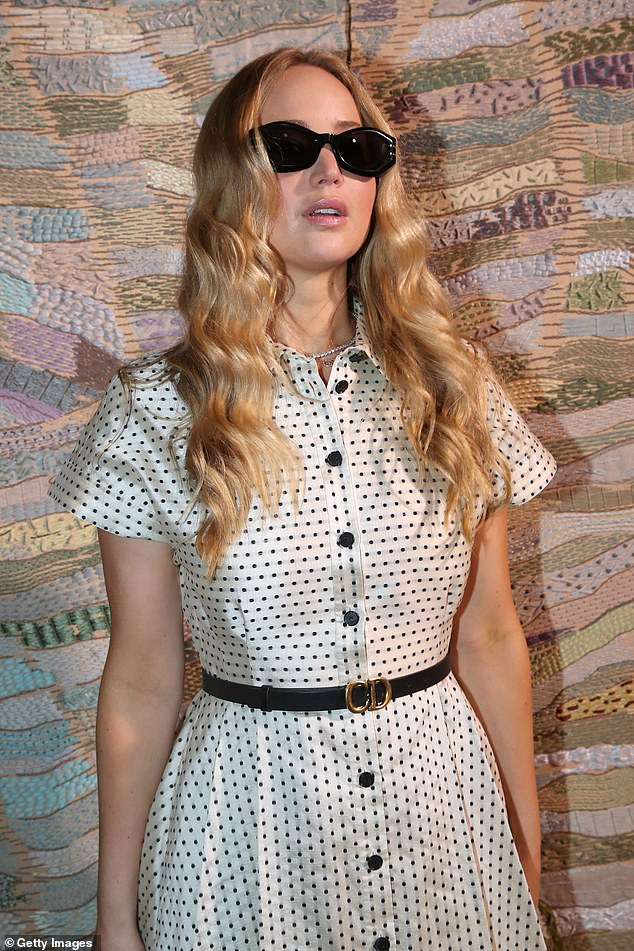 So chic! The Hunger Games star, 30, looked incredible in a polka dot dress with a monogrammed belt cinching in her waist and trendy sunglasses