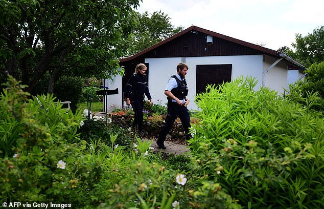 Police officers walk past the garden shed where boys were abused by Adrian V. and the three other men in April last year
