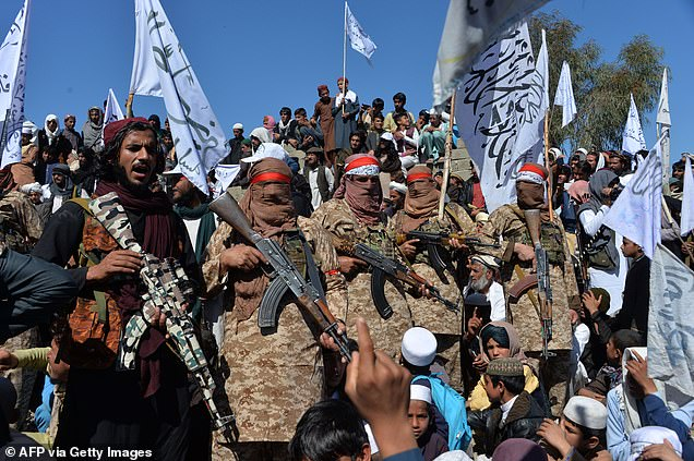The Taliban appear to be winning the propaganda war with videos to prove they will welcome surrendering soldiers (pictured, Taliban fighters and villagers on March 2, 2020)