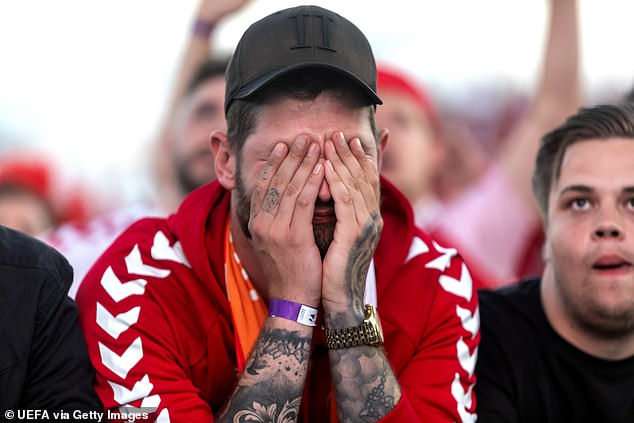 A Danish fan hides his pain behind his hands as he watches in Copenhagen after his team were dumped out of the Euros