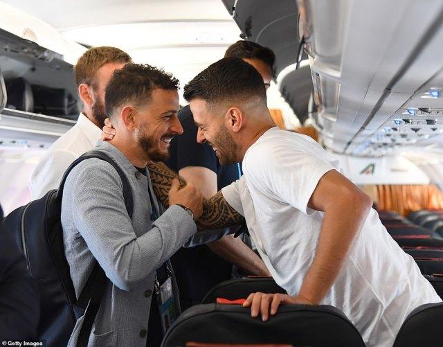 Alessandro Florenzi of Italy greets his teammate Leonardo Spinazzola on the plane during their journey to London