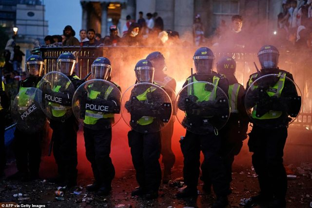 Riot police with shields are out in force as England fans mob the streets of London