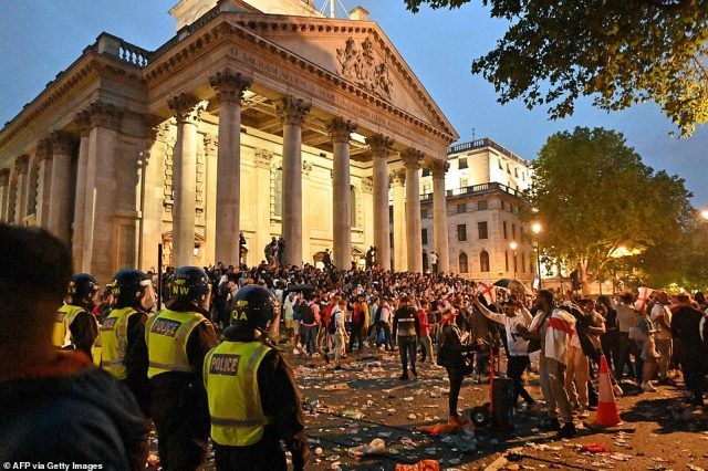 Riot police carrying shields monitor England supporters standing outside St. Martin-in-the-Fields church on the edge of Trafalgar Square