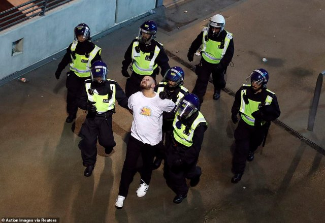 A man is led away in handcuffs after wild scenes among football fans in central London