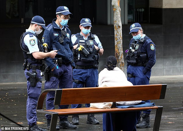 Police officers speak to a woman in Hyde Park in Sydney's CBD on Sunday as they enforce the city's three-week lockdown