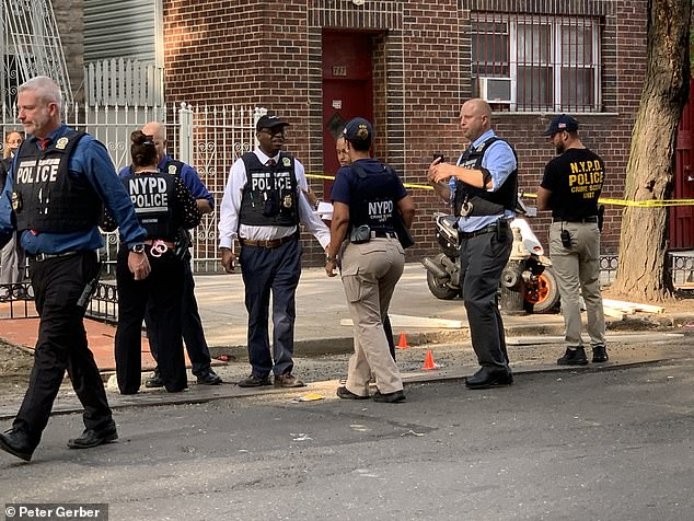 As of July 4, there have been 765 shootings throughout the city since the year began, with 886 shooting victims, according to NYPD's crime statistics. Pictured is this photo, NYPD investigate the scene outside Angels Café where 13-year-old Jaryan Elliot was shot