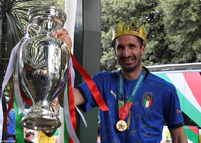 Italy captain Giorgio Chiellini holds the Euro 2020 cup as the team arrive at the Parco dei Principi hotel in Rome this morning