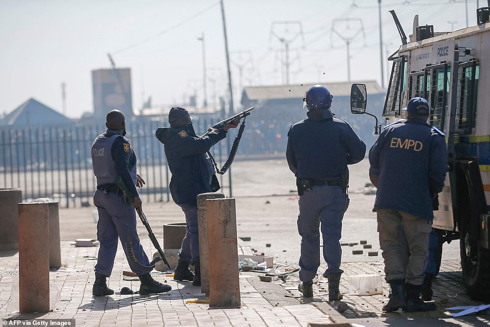 A South African police officer fires rubber bullets at a crowd of demonstrators near Johannesburg on Monday as the country descends into violence