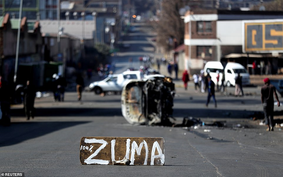 The remains of a burned-out car are seen in front of a sign left by supporters of Jacob Zuma in Johannesburg
