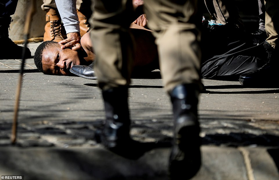 Police officers detain a person during a protest, as violence following the jailing of former South African President Jacob Zuma spread to the country's main economic hub in Johannesburg, South Africa
