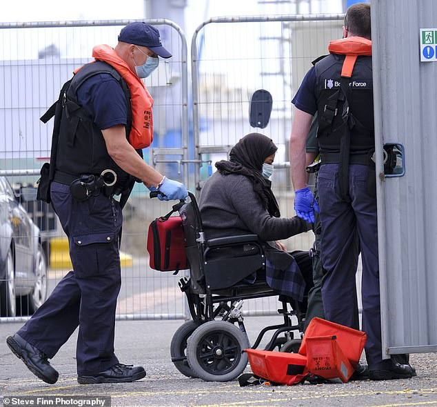 Rescue teams escort migrants as they arrive to Dover in Kent this morning