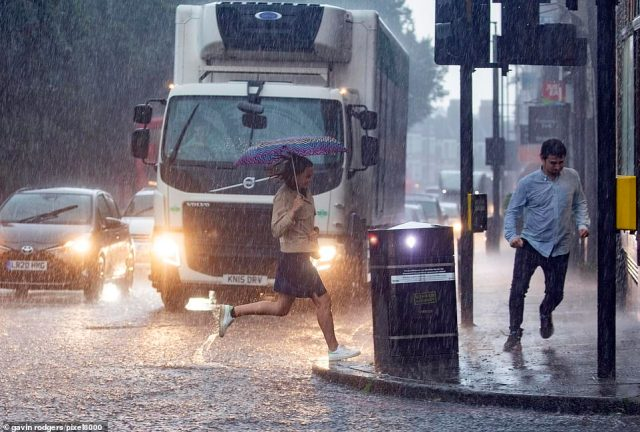 People sprint through the streets of Highgate in north London with their umbrellas to get out of the torrential downpours