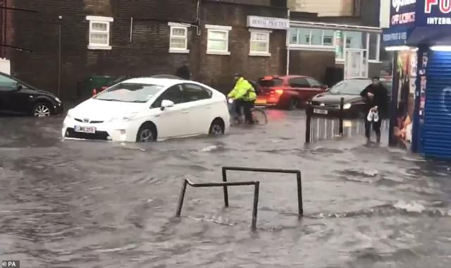 Cars are abandoned in water after torrential downpours left roads flooded in Turnpike Lane, north London, yesterday