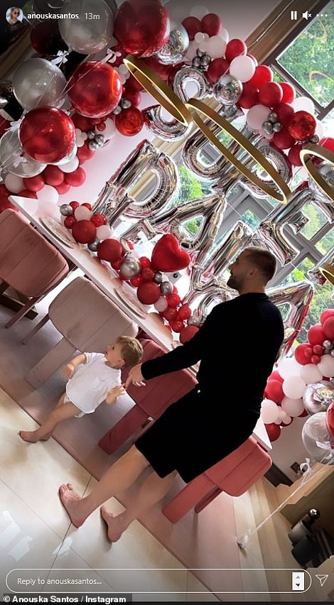 Adorable: Meanwhile Luke Shaw's girlfriend Anouska Santos set up sweet 'Super Dada' balloons and showed their son Reign London looking at them together
