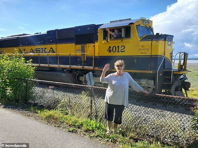 Flying by! One train driver threw an arm out the window of his vehicle, which appeared to be in Alaska, as he drove behind a woman posing for a snap