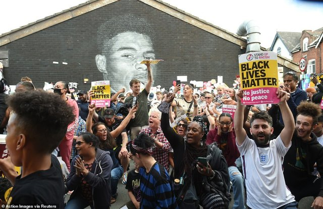 Demonstrators have been seen holding aloft signs with 'Black Lives Matter' and 'No Justice No Peace' in front of the painted tribute