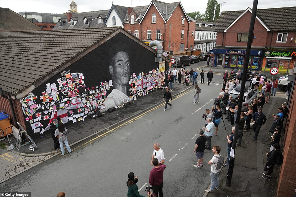 Residents gathered on the street in Withington, Manchester, to watch the mural being repainted after its was daubed with derogatory comments about Rashford