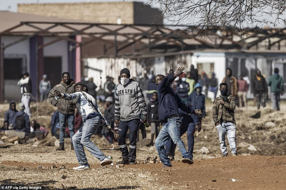 Angry locals launch rocks at police officers near the entrance of a looted shopping mall after the fifth day of ransacking in South Africa