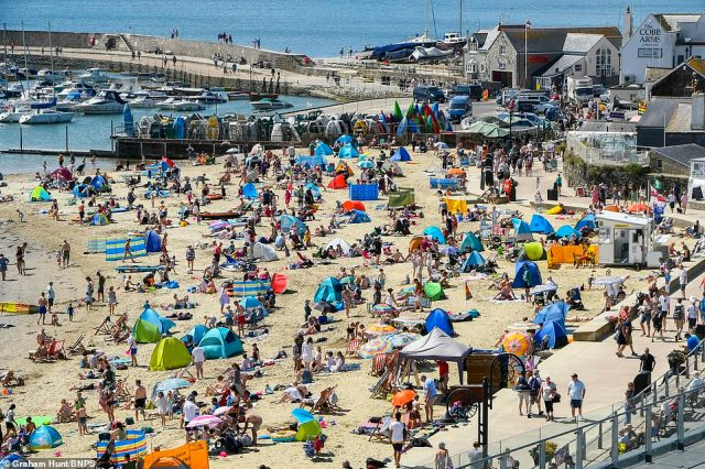 The beach is packed as families and sunbathers flock to the seaside resort in Dorset on a day of scorching hot sunshine