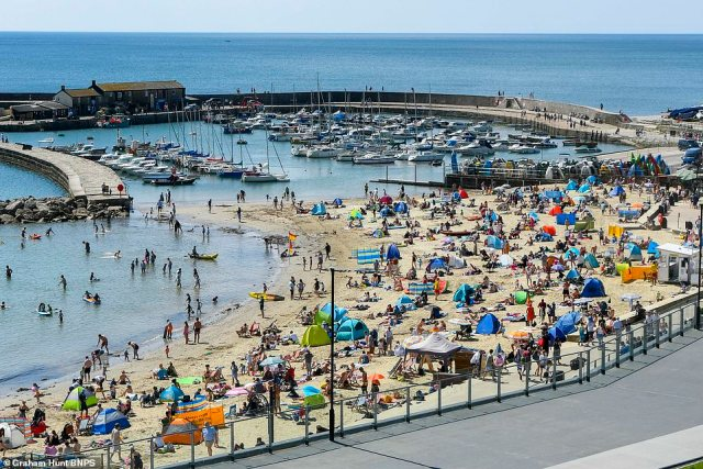 Britons could be basking in warm temperatures and sunny skies for the rest of the week and through to the weekend as temperatures could reach as high as 87F this weekend. Pictured: Families flock to Lyme Regis in Dorset to enjoy the sun today