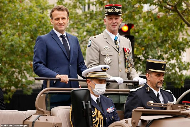 French President Emmanuel Macron and French Armies Chief of Staff General Francois Lecointre stand in the command car as they review troops prior to the annual Bastille Day military parade