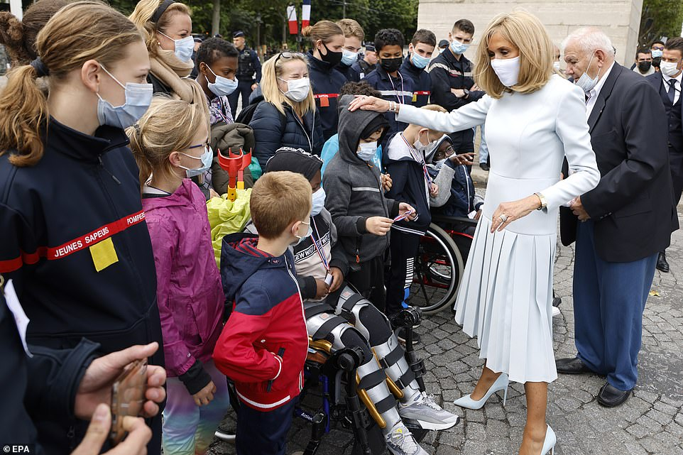 Brigitte Macron (R) meets the crowd at the end of the annual Bastille Day military parade