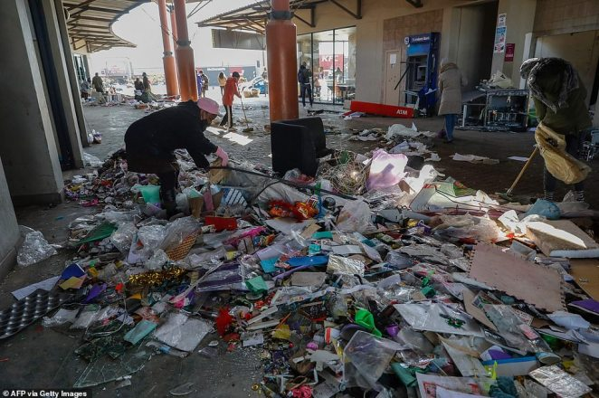 Locals use brooms while volunteering to clean the Diepkloof Square following looting and vandalism in Soweto on Wednesday morning