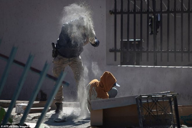 A police officer throws flour of a suspected looter before arresting him outside the Chris Hanni Mall in Vosloorus on Wednesday