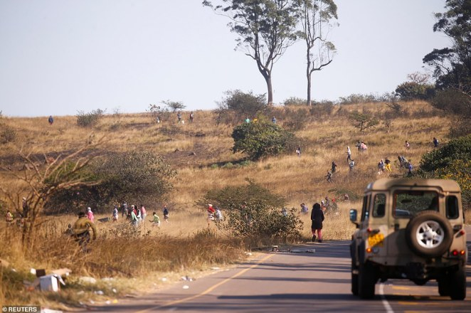 Suspected looters sprint through fields as they try to escape from police and army officers in Cato Ridge,in the KwaZulu-Natal province, on Wednesday