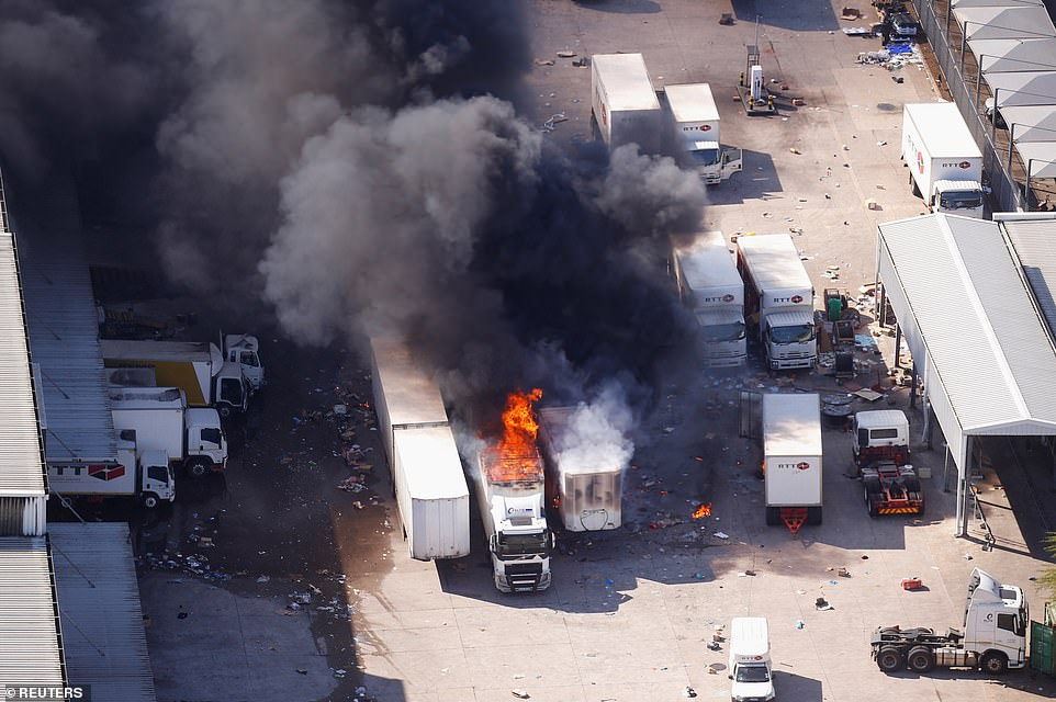 Burning lorries at a goods distribution hub on the outskirts of Durban - one of the country's major ports of entry for fuel, household goods and medicines
