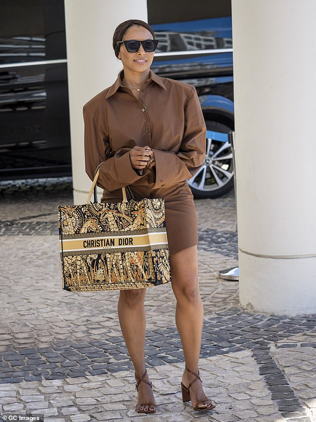 Stepping out: The garment was left unbuttoned at the collar and down by her thigh, leaving her long legs on show as she carried a Christian Dior bag upon leaving her hotel