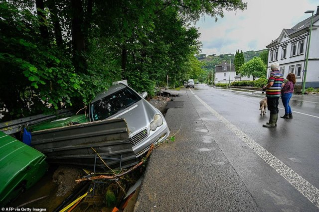 People look a at a destroyed car and other damages caused by the floods of the Volme riverin Priorei, near Hagen