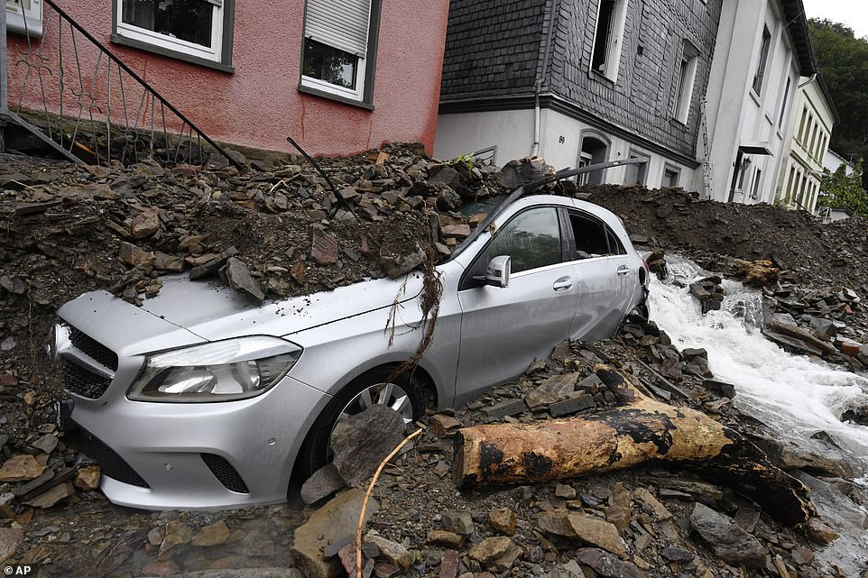 A car is seen covered in rubble in the German town of Hagen, south of Dortmund, after it was hit by flooding overnight