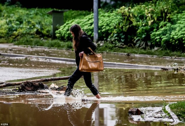 A woman wades through floodwaters in the town of Hagen after torrential rain inundated rural areas in western Germany