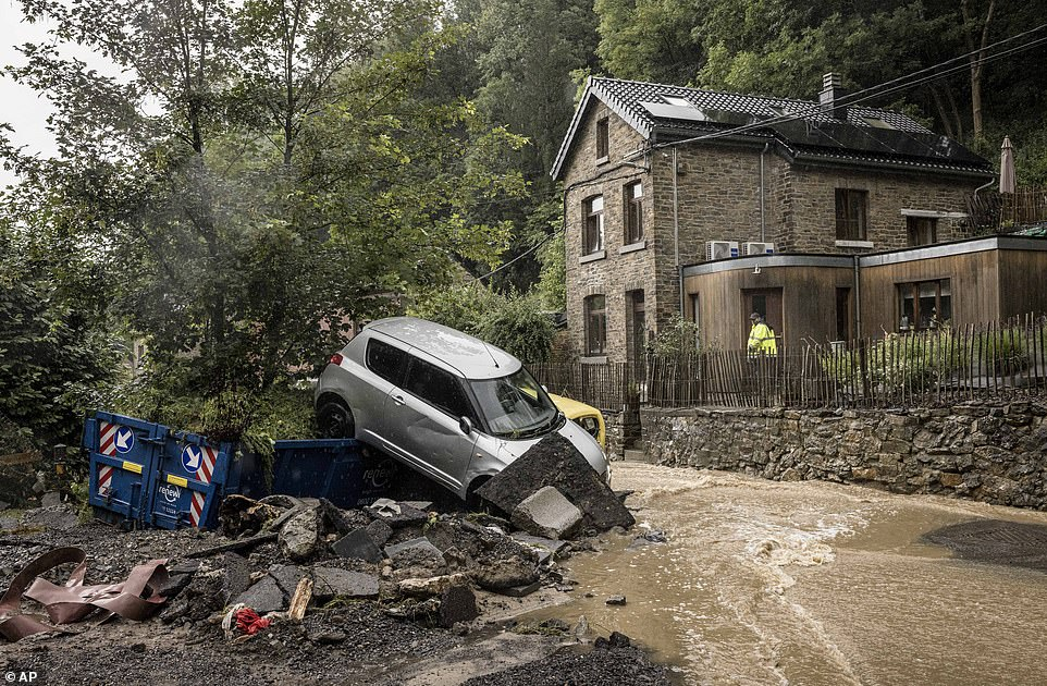 A man looks at damaged cars in a flooded street in Mery, in the Belgian province of Liege, after heavy flooding overnight