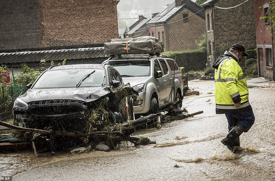 A man walks by damaged cars in a flooded street in Mery, Province of Liege, Belgium