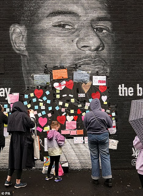 People place messages of support on top of bin liners that were placed over offensive wording on the mural of Rashford