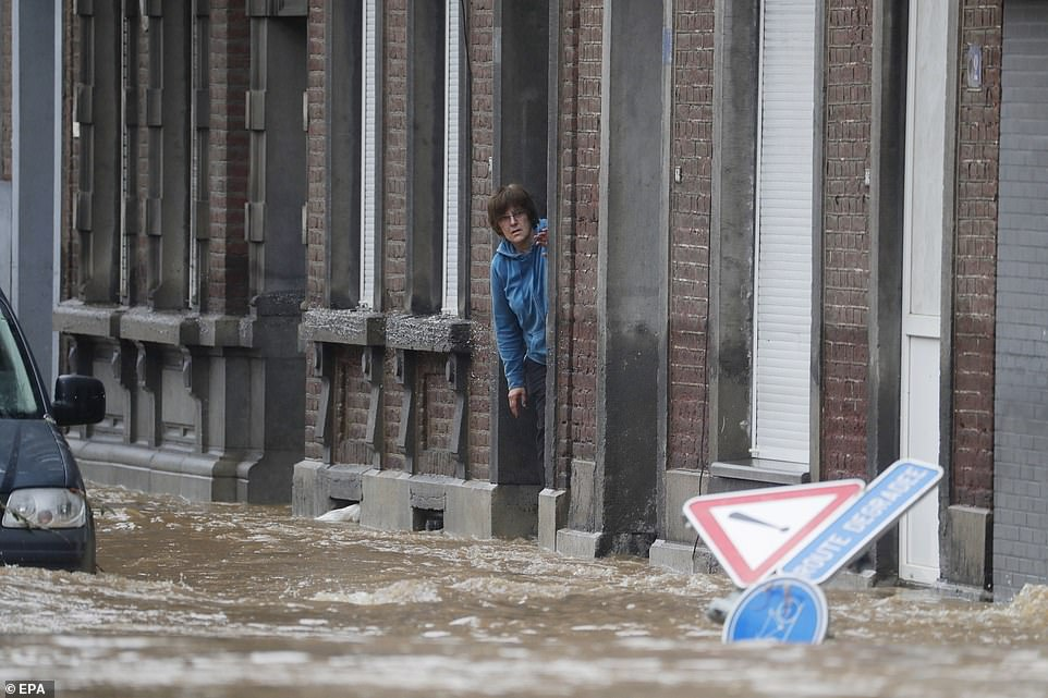 A woman looks from a building at a flooded road after heavy rains in Ensival, Belgium