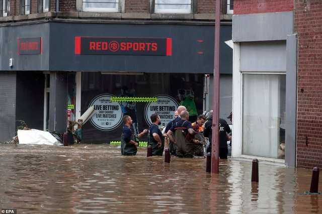 Emergency workers wade through a flooded road after heavy rains in Ensival, Verviers, Belgium
