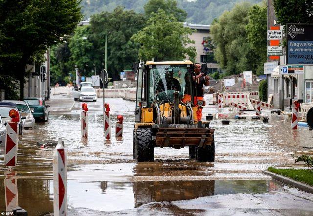 An excavator is seen on a flooded street in Hagen, Germany