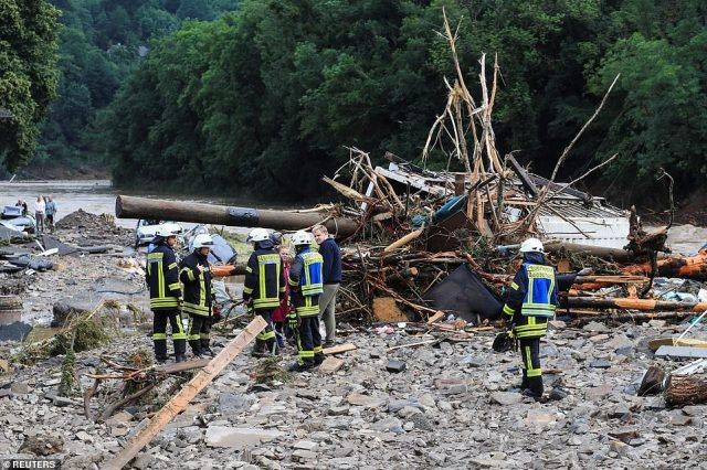Firefighters speak with people next to debris brought by the flood following heavy rainfalls in Schuld, Germany
