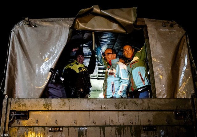 Ambulance personnel and police officers stand inside an army vehicle to evacuate residents of a care home, in the municipality of Valkenburg aan de Geul, South Limburg region, the Netherlands