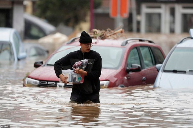 A man wades through the water as flooding affects the area after heavy rains in Ensival, Verviers, Belgium