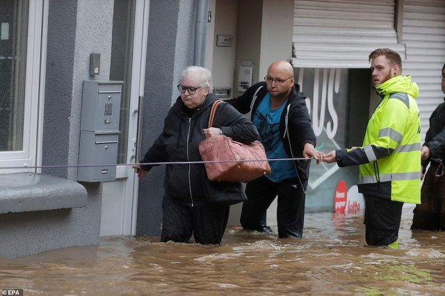 People wade through the water as flooding affects the area after heavy rains in Ensival, Verviers