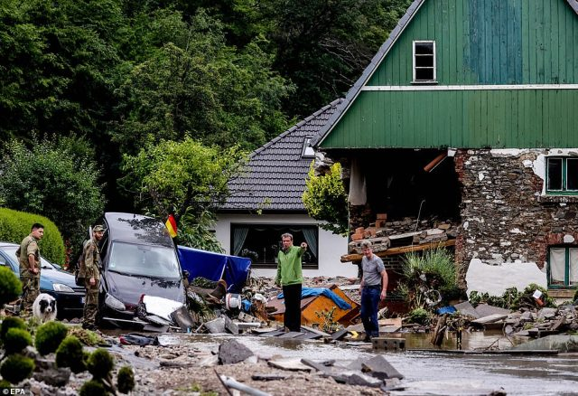 German Army soldiers and local residents try their best to clean up the damage after flooding in Hagen, Germany