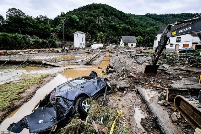 GERMANY: A digger moves debris including a smashed-up car after heavy flooding hit Schuld, in western Germany