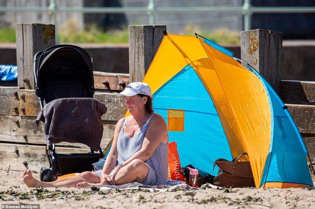A woman sits on the sand on Portobello Beach near Edinburgh as the UK braces for another heatwave