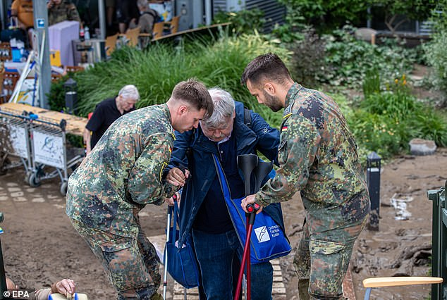 An elderly patient is assisted by soldiers as she is evacuated from a hospital inBad Neuenahr