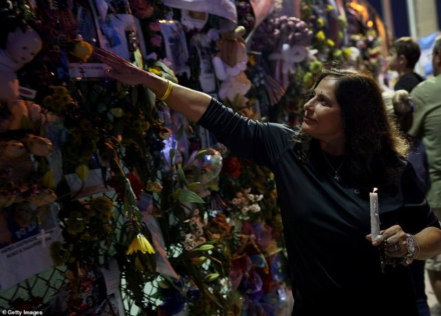 Soraya Batista visits the memorial that has pictures of some of the victims from the partially collapsed 12-story Champlain Towers South condo building on Thursday