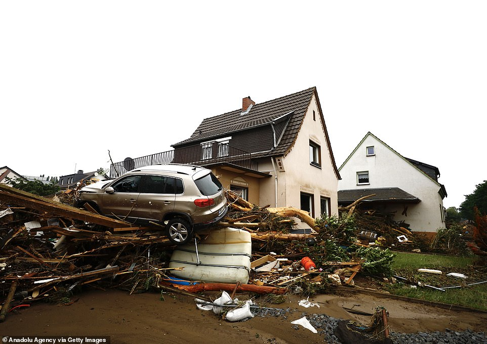 A car sits atop a mountain of debris washed that piled up against the side of a house in the Ahrweiler district of Germany